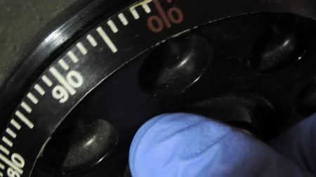 cadarço : Close up image of torchlit hand turning a combination lock dial on a safe