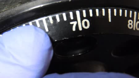 biztonság : Safe combination lock. Closeup image of torchlit hand turning a combination lock dial on a safe
