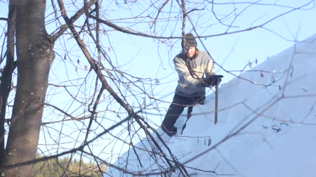 deep snow : Man removing snow from the roof with a shovel