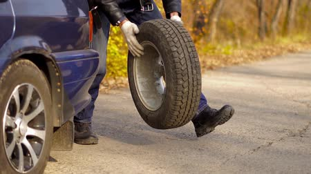 unscrewing : a man rolls a tire