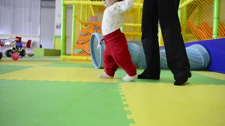 step : First steps of walking baby with mother. Tracking shot Stock Footage