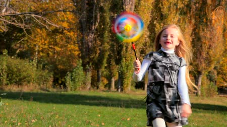 moinho de vento : Happy little girl running with pinwheel in the hands