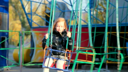 autumn : Child on swing in amusement park Stock Footage