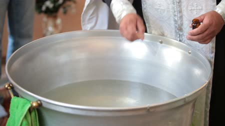 благодать : priest blesses baptismal font before the christening