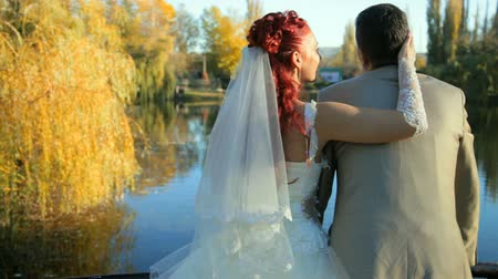 vöröshajú : Newlyweds embracing in the autumn city park Stock mozgókép