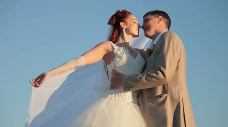 redhead suit : Newly married couple kissing against the blue sky Stock Footage