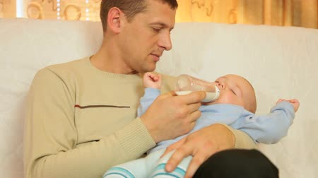 holding : Father feeding his baby boy at home Stock Footage