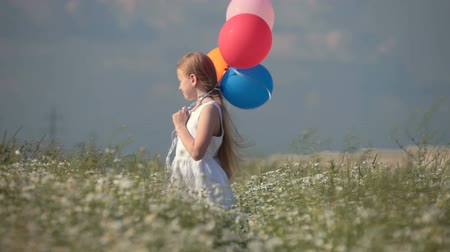 луг : Child with balloons on spring blooming meadow