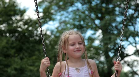 small park : Little girl on the playground swinging Stock Footage
