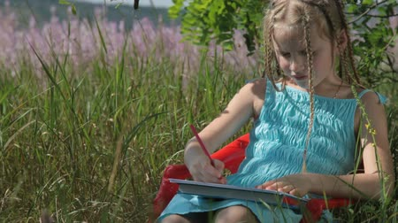 kreslit : Little girl drawing with colored pencils on the nature Dostupné videozáznamy