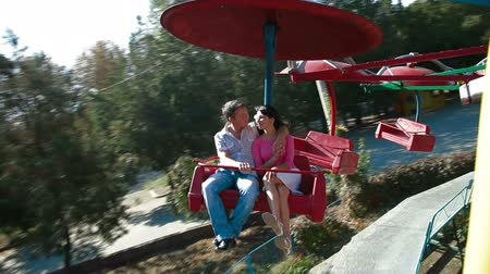 kolotoč : A young couple spinning on a carousel in amusement park