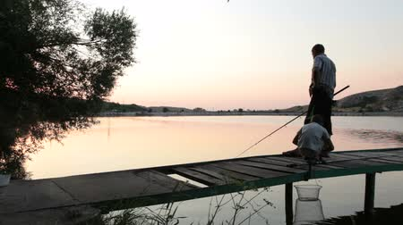 otec : Father and son fishing at dusk by the lake