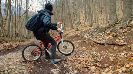 teen action : Teen boy rides a bicycle in the autumn forest