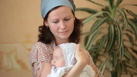 держит : Mother with a baby on hands at the christening Стоковые видеозаписи