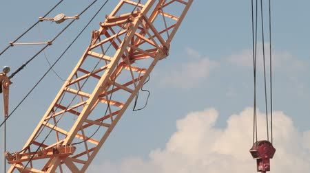 Construction crane lifting cargo at the construction site Wideo