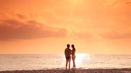 Young couple embracing on the beach at sunset