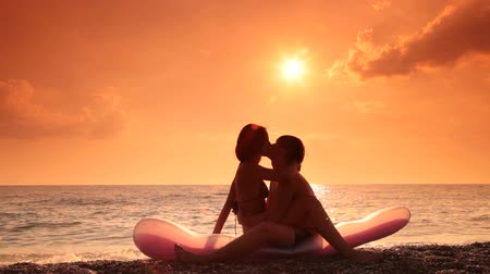 zakochani : lovers kissing on the beach on the background of the setting sun Wideo