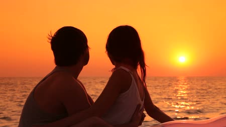 Young couple on lonely beach at sunset