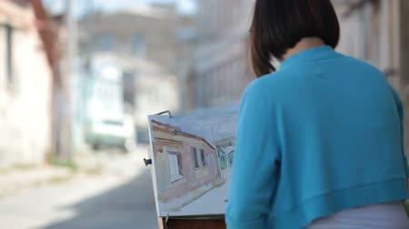 Young girl painter painting a cityscape with watercolor Wideo