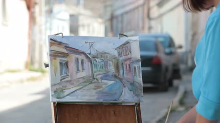 Young girl painter painting old street with watercolor Wideo