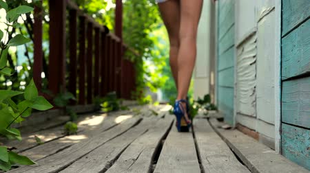 vysoký : Young woman in fashionable high heeled platform shoes walking along old wooden porch