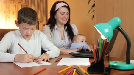 Mother with two children sitting at a table with a laptop at home, working or surfing the net