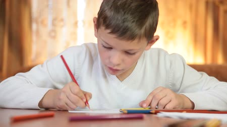 Cute little boy drawing or doing homework at the table in living room