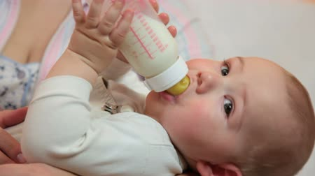 infant formula : Cute baby boy drinking milk formula from a bottle on his mothers arms at home