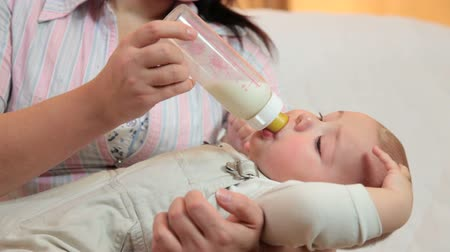 Young mother feeding her baby boy milk formula from a bottle in the living room Wideo