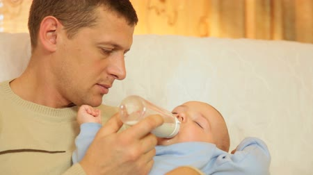 Young father feeding her baby boy milk formula from a bottle in the living room Wideo