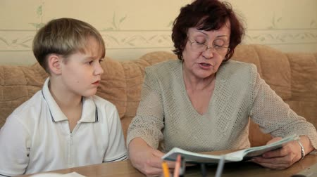 schoolbook : Grandmother with her grandson doing homework sitting at a desk in the living room