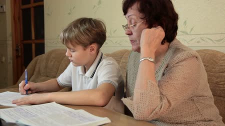 schoolbook : Grandma helping her grandson doing homework sitting at a desk in the living room Stock Footage