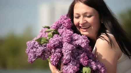 Face of happy young woman with a bouquet of lilacs in the spring close up Wideo