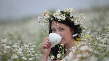 young woman drinking from a cup sitting among the daisies on the lawn