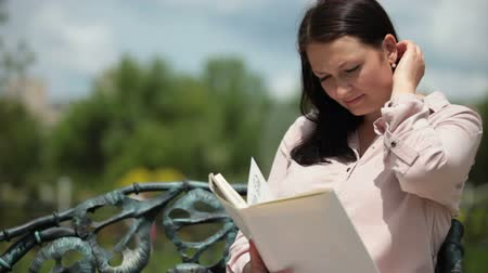 Pregnant young woman sitting on a park bench reading a book in the summer Wideo