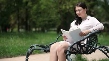 enciclopédia : Pregnant young woman sitting on a park bench reading a book in the summer Stock Footage