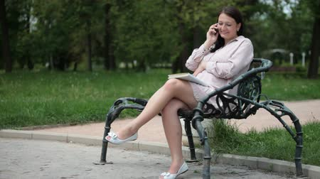 Pregnant young woman sitting on a park bench speaks by phone