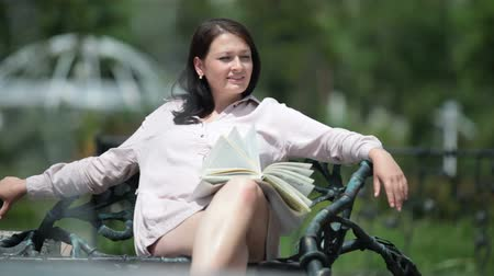 Young pregnant woman relaxing on a bench in a city park reading a book in the summer Wideo