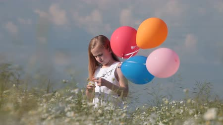balonlar : little blonde girl with colorful balloons in lush summer field Stok Video