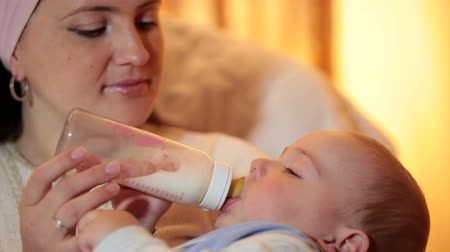 мама : Young mother feeding baby boy milk formula from a bottle in the living room closeup Стоковые видеозаписи
