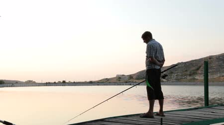 Man with fishing rod by the lake in the summer