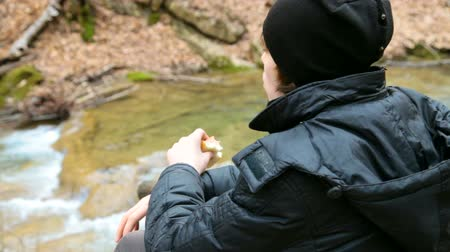 Hiking boy having lunch on nature in the woods near river Wideo