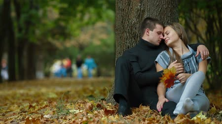 Young couple kissing on fallen leaves in autumn park Wideo