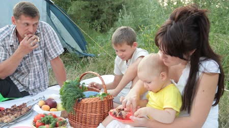 пикник : Young family with children spending weekend on the nature eating shashlik at picnic near camp tent