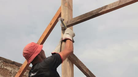 vállalkozó : Construction roofer nailing wood board with hammer on roof installation work