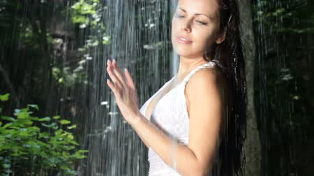 young woman standing under streams of falling water in the forest Wideo