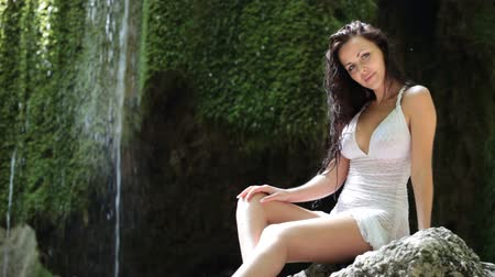 Young woman resting at a mountain waterfall in the summer woods looking at the camera smiling Great Canyon of the Crimean Mountains Silver jet Wideo
