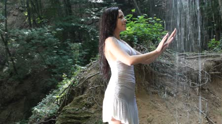 young woman refreshing under streams of falling water in the summer forest