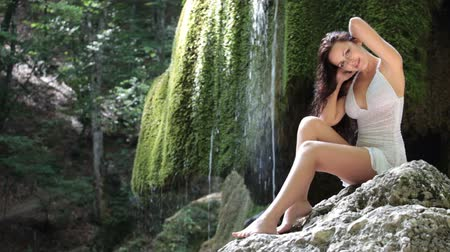 young woman posing near a mountain waterfall in the summer woods looking at the camera smiling Grand Canyon Crimean Mountains Silver jet