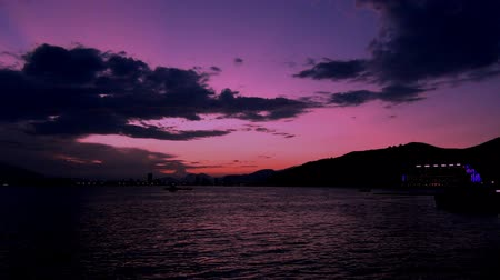 фиолетовый : Beautiful pink sunset over the mountains in the background of the sea